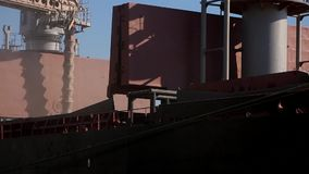 Close panorama of ship loading grain crops on bulk freighter via trunk to open cargo holds at silo terminal in seaport. Panorama of ship loading grain crops on stock video