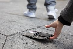 Person Picking Up A Lost Wallet. Close Of A Person Picking Up A Lost Wallet On Street royalty free stock photos