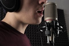 A close photo of the male lips singing at the microphone on the counter. Horizontal photo Stock Photo
