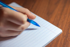 A close photo of a persons writing a letter with a pen Royalty Free Stock Images