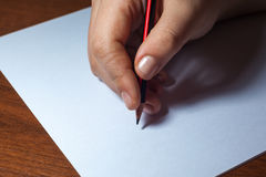 A close photo of a persons writing a letter with a pencil.  Royalty Free Stock Photography