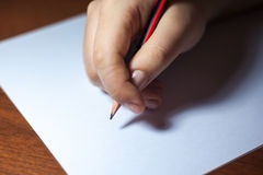 A close photo of a persons writing a letter with a pencil Royalty Free Stock Image