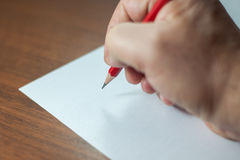 A close photo of a persons writing a letter with a pencil Stock Photo