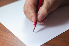 A close photo of a persons writing a letter with a pencil.  Royalty Free Stock Images
