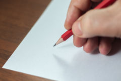 A close photo of a persons writing a letter with a pencil Stock Images