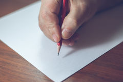 A close photo of a persons writing a letter with a pencil Royalty Free Stock Images