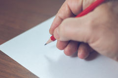 A close photo of a persons writing a letter with a pencil.  Stock Photos