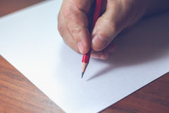 A close photo of a persons writing a letter with a pencil.  Stock Images