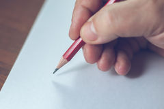 A close photo of a persons writing a letter with a pencil Stock Image