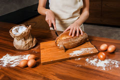 Close picture of hands cutting fresh bread Royalty Free Stock Image