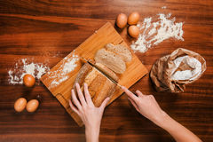 Close picture of hands cutting fresh bread Royalty Free Stock Images