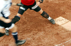 Close play. A close play at first base in a softball game. Motion blurred Stock Image