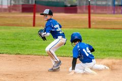 Close play at second base. Youth baseball player in blue uniform playing short stop avoiding the sliding base runner and preparing to throw the ball royalty free stock images