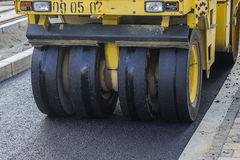 Close of pneumatic tyred roller compacting asphalt Stock Photo