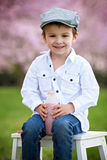 Close portrait of adorable little caucasian boy in a cherry tree Stock Photo