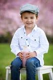 Close portrait of adorable little caucasian boy in a cherry tree Stock Photo
