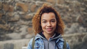 Close portrait of African American girl with light curly hair wearing casual clothing looking at camera and smiling stock video