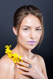 Close portrait of beautiful naked girl with bright makeup and manicure holding a blossoming branch. Royalty Free Stock Photo