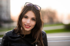 Close portrait of beautiful smiling dark-haired young woman, against summer green park on the sunset Stock Photography