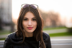 Close portrait of beautiful smiling dark-haired young woman, against summer green park on the sunset Stock Image