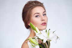 Close portrait of a beautiful young girl with lily flowers. Royalty Free Stock Photography