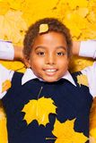 Close portrait of a black boy in autumn leaves Stock Image