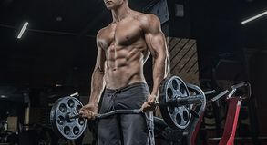 A close portrait of a bodybuilder, coaches a biceps using sports. The bodybuilder does exercises for the development of the muscles of the biceps using the stock photo