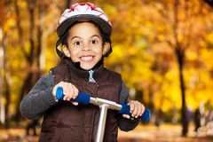 Close portrait of boy riding a scooter Royalty Free Stock Image