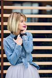 A close portrait of a dreamy girl with bright pink lips and short blond hair looking to her left listening to music on a.  royalty free stock photography