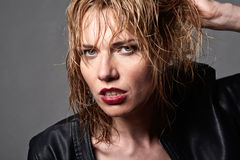 Close portrait of edgy young blond fashion model with wet hair &. Close portrait of edgy blond fashion model with wet hair & leather jacket,  isolated over Stock Photos