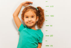 Close portrait of a girl show height on wall scale. Close portrait of little girl standing by the scale drawn on the wall in living room and measure her height royalty free stock images
