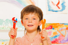 Close portrait of happy boy holding wrenches Royalty Free Stock Photos