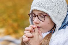 Close portrait of little beautiful cute girl teenager with glasses and cozy scarf praying makes a wish. Close portrait of a little beautiful cute girl teenager stock images