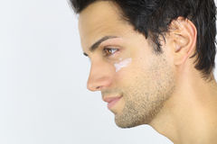 Close portrait of a man with moisturizer on her face. Portrait of an handsome man with moisturizer on her face over a white background Stock Photography