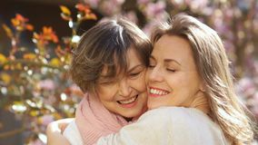 Close portrait of mature mother and adult daughter hugging. Two women love each other, mother`s day stock video footage