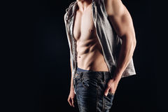 Close portrait of a naked torso. A man in a shirt undone, a denim outfit. Naked torso muscles cubes. Posing in the Royalty Free Stock Images