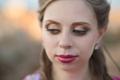 Close portrait of Pretty young blond lady woman with huge beautifull green eyes and pout red lips wearing dark pink dress.Make up. Picture of adoreable beauty royalty free stock images