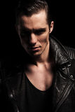Close portrait of rocker in leather jacket posing in dark. Close portrait of sexy rocker in black leather jacket posing in dark studio backgound looking at the Royalty Free Stock Image