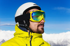 Close portrait of skier man. Close profile portrait of a man with beard wearing ski mask and helmet over mountains Stock Photo