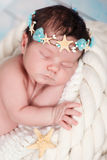 Close portrait of a sleeping newborn girl in the maritime hoop of starfish and pearls Royalty Free Stock Images