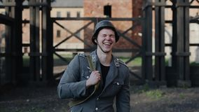 A close portrait view of a laughing young German soldier. Blurred concentration camp on the background. World War 2. A smiling young handsome actor dressed as a stock video