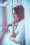 Close portrait of woman, looking through a window at home Royalty Free Stock Photography