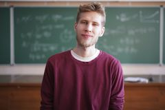 Close portrait of young bearded professor teacher in casual with blackboard with formulas behind. Close up portrait of young bearded professor teacher in casual stock image