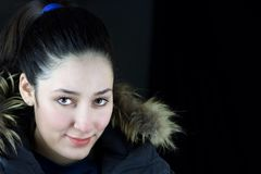 Close portrait of young brunette in winter clothes. Dark background Stock Photography