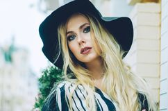 A close portrait of a young fashionable blonde in a black hat. Autumn. Fashion photo. Street photos. A close portrait of a young fashionable blonde in a black Stock Photos
