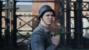 A close portrait of a young German soldier with a rifle looking straight, turning his head to the right, and looking at. WW2 reenactment. A close side view of a stock video footage