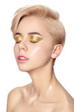 Close portrait of young girl with golden glitter eyeshadow Stock Photography