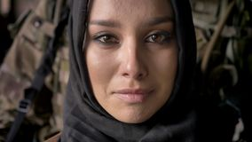 Close portrait of young muslim woman in hijab crying and looking at camera, armed soldier with weapon standing behind stock video footage