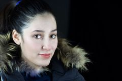 Close portrait of young woman in winter clothes. And hair tied to ponytail Royalty Free Stock Image