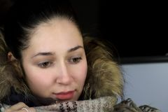 Close portrait of young woman in winter clothes. Looking down Stock Image